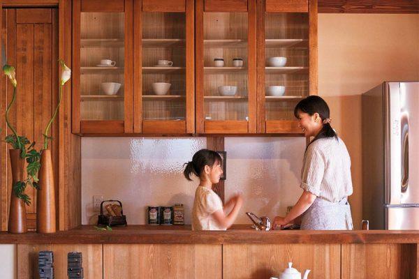 郷の家のキッチンで料理をする親子